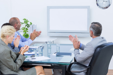 board room: Business team applauding and looking at white screen in the meeting room Stock Photo