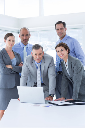 board room: Business team working happily together on laptop in the office Stock Photo