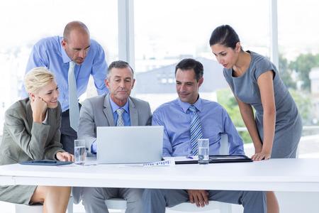 reuniones empresariales: Equipo de negocios trabajando juntos en la computadora port�til en la oficina