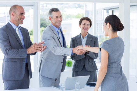 Interview panel shaking hands with applicant in the office