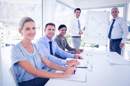 reuniones empresariales: Equipo de negocios durante la reunión sonriendo a la cámara en la oficina