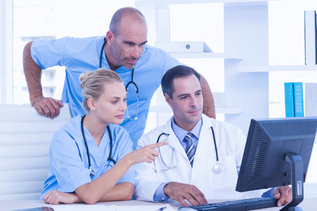 medical doctors: Teams of doctors working on laptop computer in medical office Stock Photo