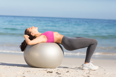 ball stretching: Fit woman stretching on exercise ball at the beach