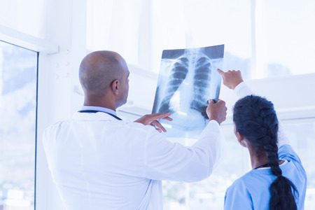 medical doctors: Doctors analyzing together xray in medical office