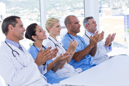 Team of doctors applauding during meeting in medical office