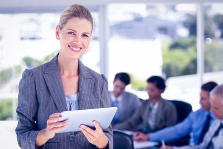 together standing: Businesswoman holding tablet and looking at camera in the office