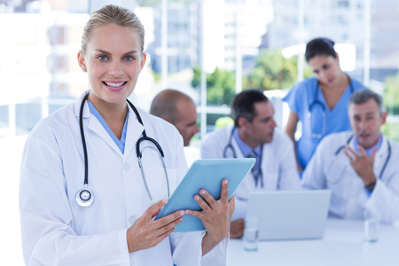 medical team: Smiling female doctor looking at clipboard while her colleagues works lo