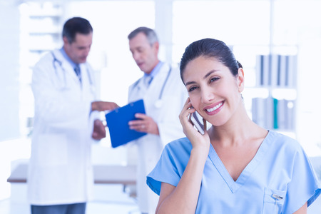 doctors smiling: Smiling female doctor phoning in the hospital Stock Photo