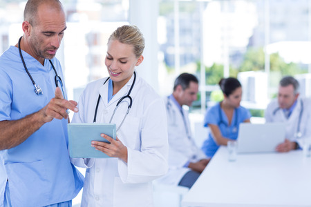 Two doctors looking at clipboard while their colleagues working in medical office Stockfoto