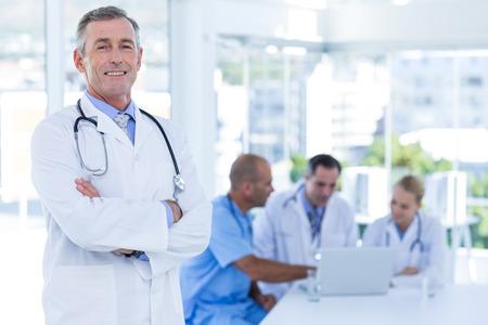 doctores: Doctor feliz mirando a la c�mara con los brazos cruzados mientras sus colegas trabaja en el consultorio m�dico