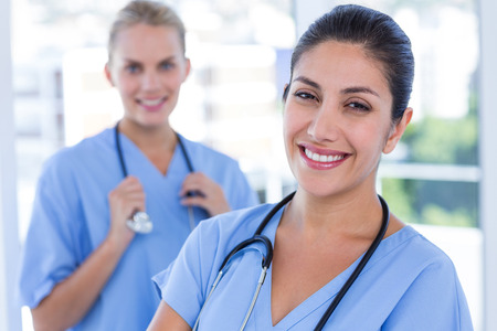 medical doctors: Happy doctors looking at camera in medical office Stock Photo