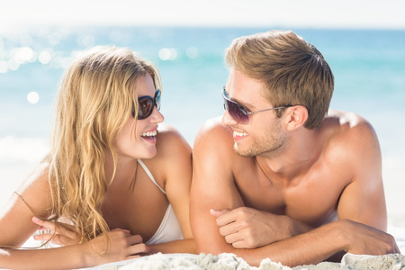 escapism: Happy couple relaxing together in the sand at the beach Stock Photo