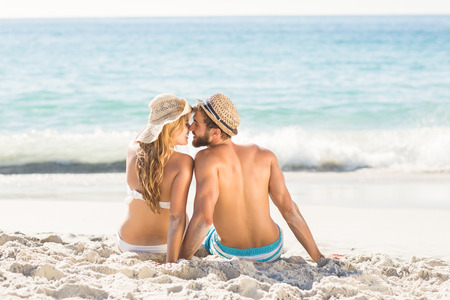 love kissing: Happy couple relaxing together in the sand at the beach Stock Photo