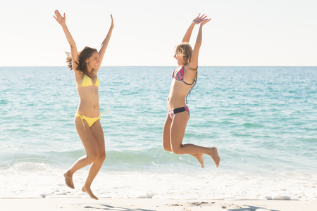woman portrait: Happy friends jumping together at the beach