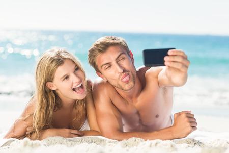 Pares felizes que tomam selfie na praia
