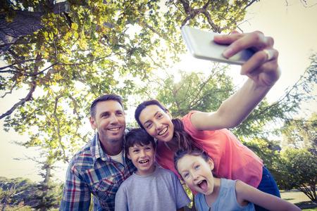 familia: Familia feliz en el parque tomando Autofoto en un día soleado Foto de archivo