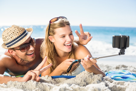stick people: Happy couple taking selfie with selfie stick at the beach