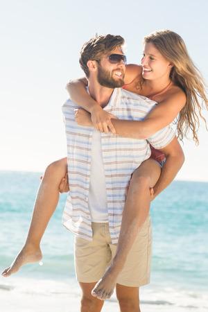 bel homme: Handsome homme donnant piggy back � sa petite amie � la plage