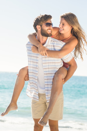 man holding: Handsome man giving piggy back to his girlfriend at the beach