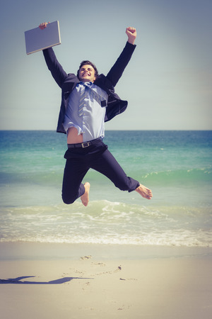 Excited businessman wearing a suit is jumping on the beach Stock Photo