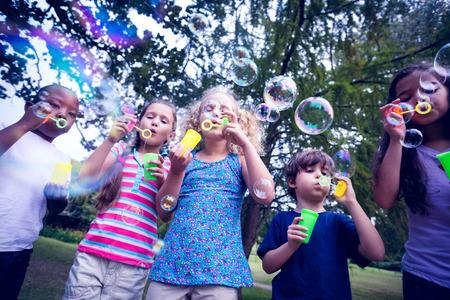 niños jugando en el parque: Niños jugando con la varita de la burbuja en el parque en un día soleado