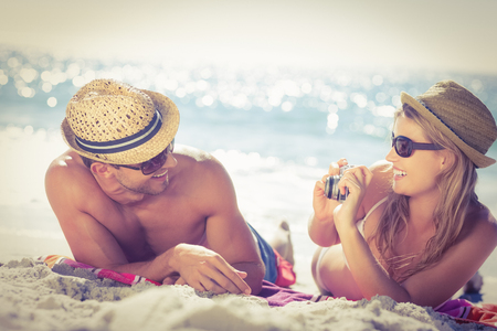 summer holiday bikini: Cute couple wearing straw hat taking photos on the beach