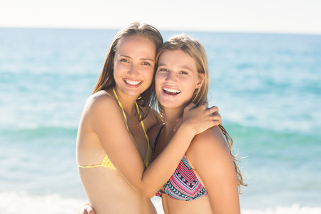 arm around: Beautiful women standing together arm around at the beach Stock Photo