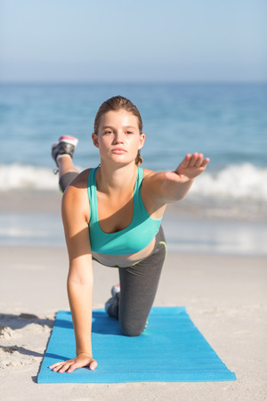 beach mat: Fit woman stretching on exercise mat at the beach Stock Photo