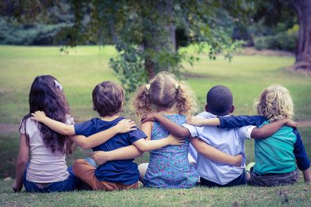 晴れた日に公園のバックになって座っている子どもたち 写真素材