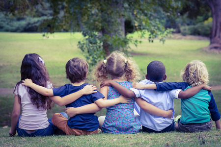 Back turned sitting children in the park on a sunny day