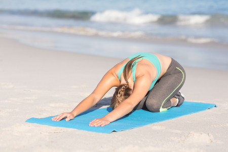 beach mat: Fit woman stretching her back on exercise mat at the beach