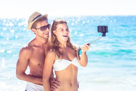 mujeres juntas: Pares felices que toman selfie con palo selfie en la playa Foto de archivo