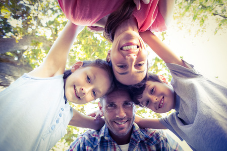huddling: Happy family in the park huddling in circle on a sunny day Stock Photo