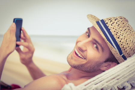 hammock: Apuesto hombre de mensajes de texto en la hamaca en la playa Foto de archivo