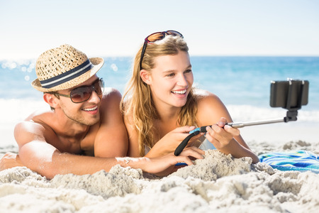 stick: Happy couple taking selfie with selfie stick at the beach