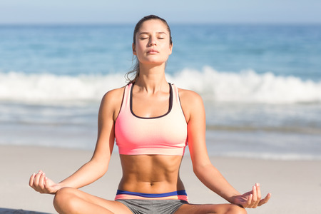closes eyes: Fit woman doing yoga beside the sea at the beach