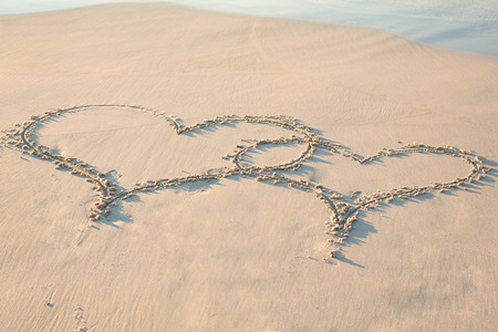 two hearts drawn in the sand on the beach