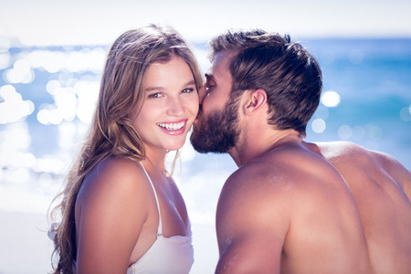 women kissing women: Handsome man receiving kiss from his gilfriend at the beach
