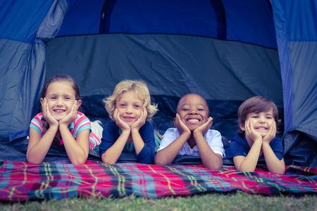 Lachende kinderen liggen in de tent samen in het park op een zonnige dag Stockfoto