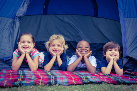 kid portrait: Smiling children lie down in the tent together in the park on a sunny day