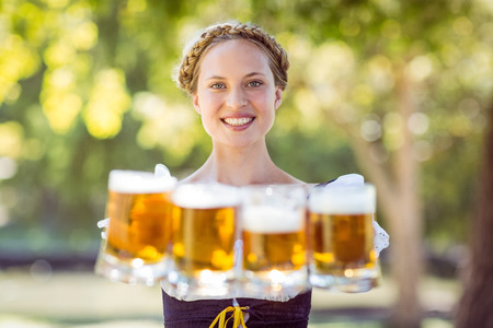 beautiful blonde woman: Pretty oktoberfest blonde holding beers on a sunny day Stock Photo