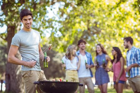 quincho: Amigos felices en el parque que tiene barbacoa en un d�a soleado