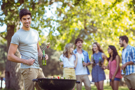 barbecue: Happy friends in the park having barbecue on a sunny day Stock Photo