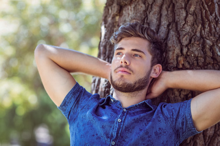 young  brunette: Handsome hipster relaxing in the park on a summers day