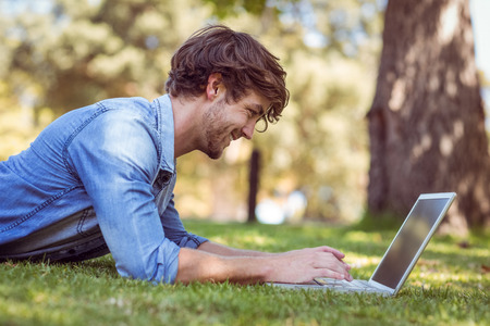 spring season: handsome hipster using laptop in park on a summers day Stock Photo