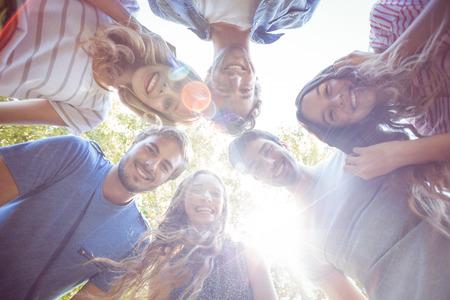 dia soleado: Amigos felices que amontonan en c�rculo en el parque en un d�a soleado
