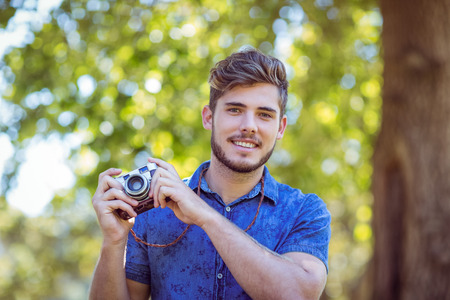 summers: Handsome hipster holding vintage camera on a summers day Stock Photo