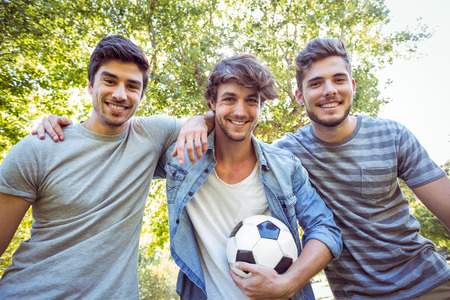 young adult men: Happy friends in the park with football on a sunny day Stock Photo
