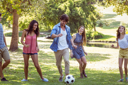 young tree: Happy friends in the park with football on a sunny day Stock Photo