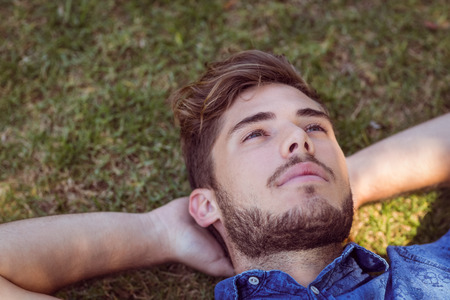 man lying down: Young man lying down in the park on a summers day Stock Photo